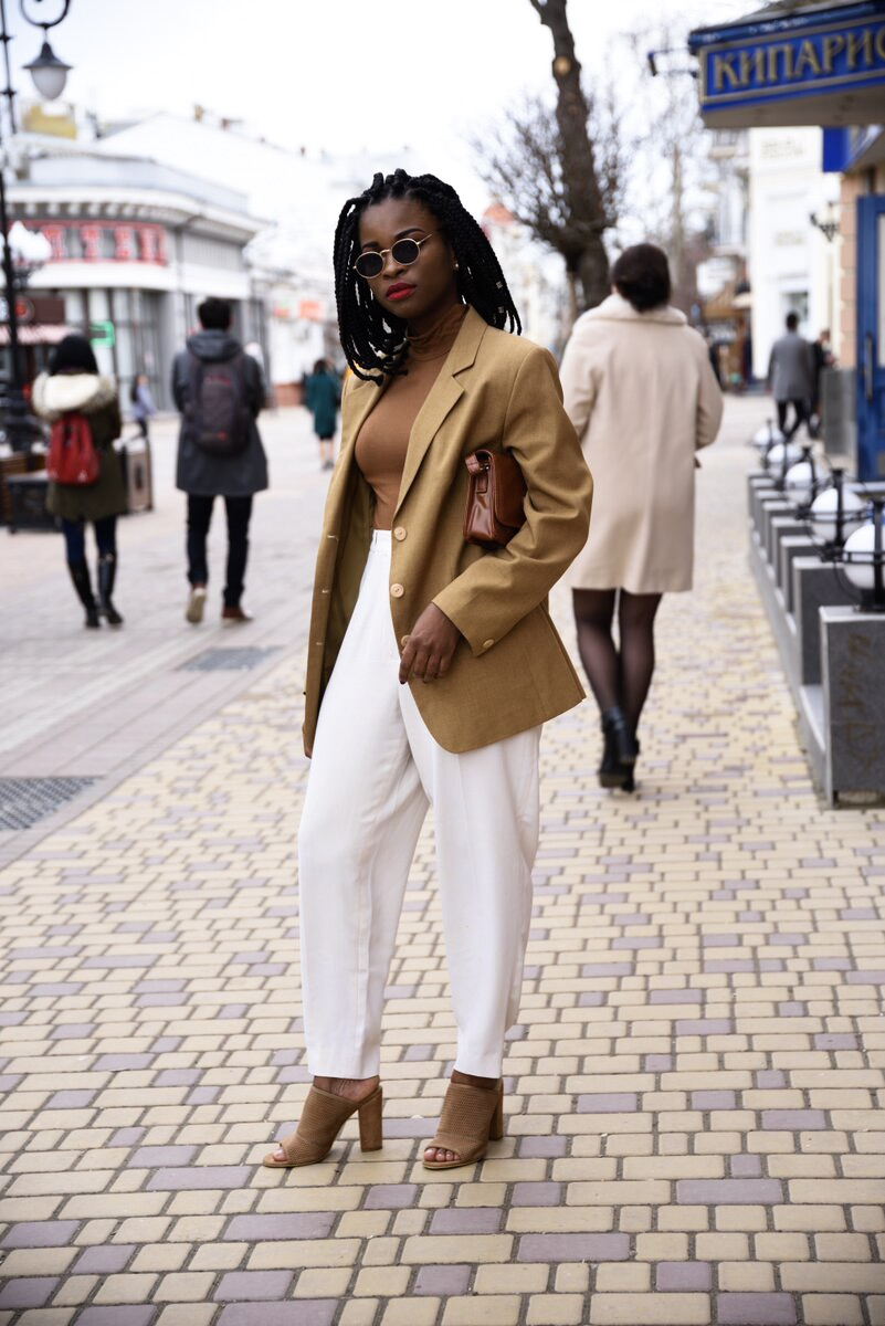 Wearing a brown blazer with turtleneck and white pants